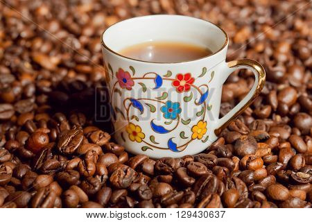 Coffee cup with floral patterns and background with coffee beans.
