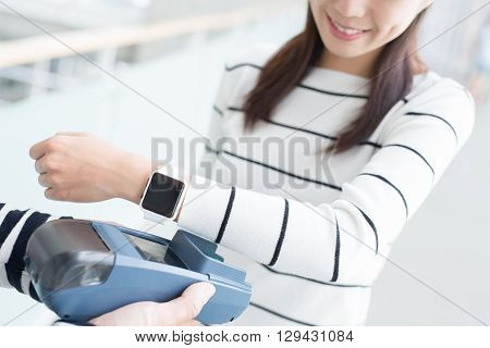young woman pay by smart watch with empty screen great for your designasian beauty
