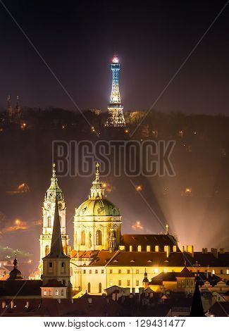 Tower of St. Nicolas church with Petrin tower during foggy night Prague Czech republic