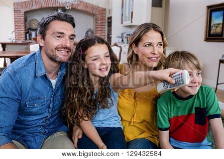 Parents and son watching television in living room at home