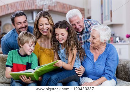 Multi-generation family looking at a photo album at home