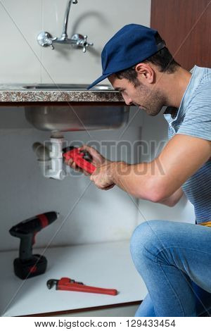 Cropped man using pipe wrench while fixing sink pipe in kitchen