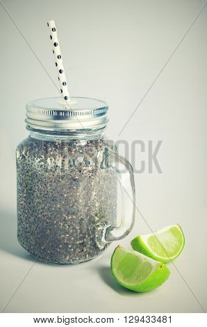 Refreshing chia seeds drink with water coconut milk and lime in mason jar and white polka dot paper straw. Toned.