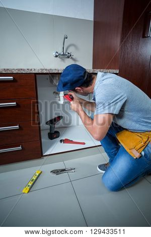 Full length of man using pipe wrench in kitchen
