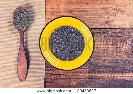Chia jelly in a plate with spoon full of dry chia seeds on grunge wooden background. Toned.