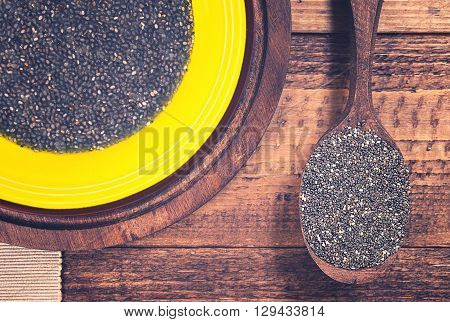 Chia jelly and chia seeds in spoon on grunge wooden background. Toned.
