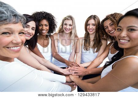 Portrait of women in a circle putting their hands together on white background