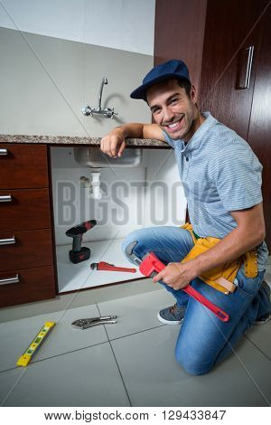 Portrait of happy man holding pipe wrench in kitchen