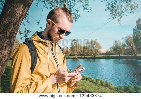 Outdoor summer lifestyle portrait of young bearded man using white smartphone in summer park. Hipster style guy with sunglasses, dressed in trendy yellow jacket, black backpack on his shoulder. Serious young male hand holding and touch mobile phone.