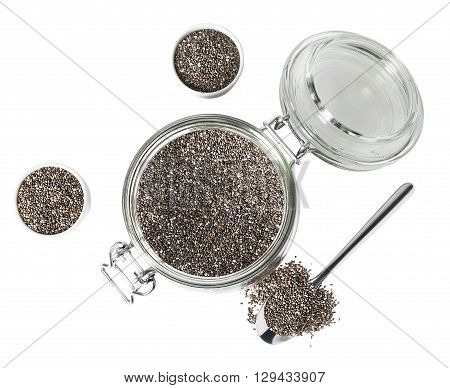 Dry chia seeds in glass jar small cups and spoon isolated on white background. Top view.