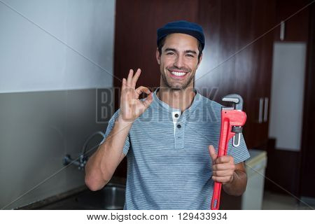Portrait of happy man showing ok sign while holding pipe wrench in kitchen