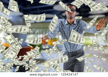 Blindfolded businessman with arms out against college