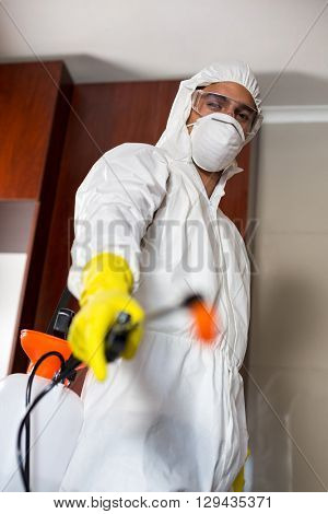 Low angle portrait of pest worker with sprayer standing in kitchen at home