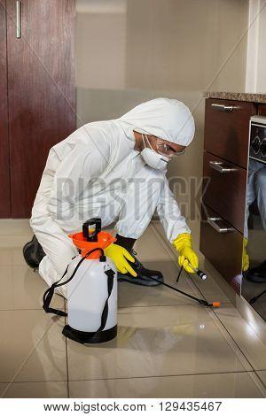 Worker using flashlight and sprayer under cabinet in kitchen at home