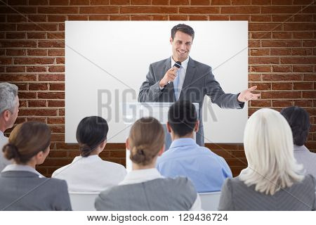 Businessman doing speech during meeting against red brick wall