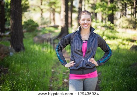 Portrait of happy female jogger standing with hands on hip in forest