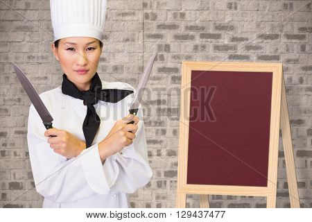 Confident female cook holding knives in kitchen against stone wall