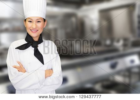 Portrait of smiling female cook in kitchen against a cooker