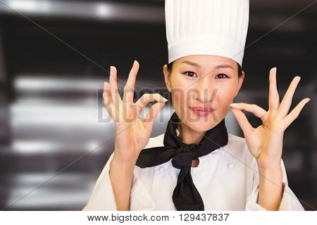 Closeup of a smiling female cook gesturing okay sign against deep fat fryers