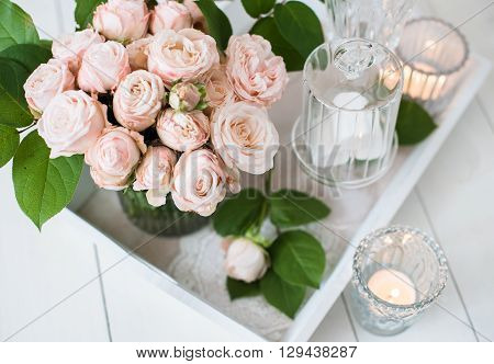 Beautiful vintage wedding table decorations with roses, candles, cutlery and  sweets in a jar.