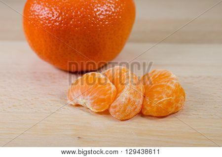tangerine segments and whole tangerine on a wooden table