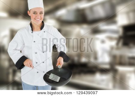 Portrait of chef using spetula and frying pan against work surface and kitchen equipment