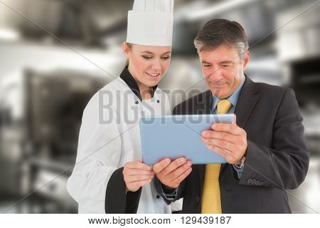 Businessman and female chef using digital tablet against work surface and kitchen equipment