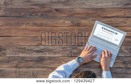 Man working on computer presentation sitting at unusual handcrafted rough wooden desk overhead top view soft sunlight large copy space
