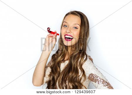 people, style, holidays, celebration and fashion concept - happy young woman or teen girl in fancy dress with sequins and party horn