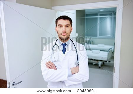 clinic, profession, people, health care and medicine concept - doctor with stethoscope at hospital corridor
