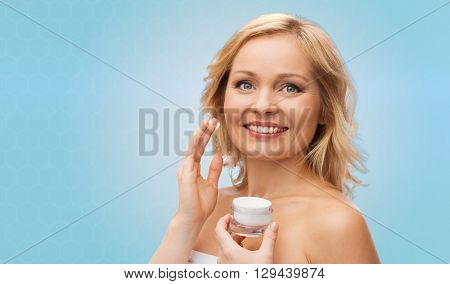 beauty, people, skincare and cosmetics concept - happy woman applying cream to her face over blue background