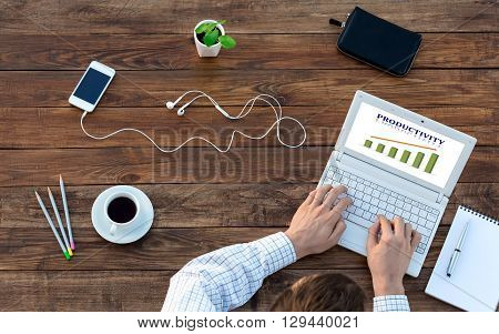 Natural Rough Wooden Desk Man Working Computer Top View Smart Casual Clothing Typing Keyboard with Productivity Chart on Screen Smart Phone and Cup of Coffee