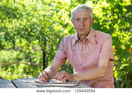 portrait of senior man sitting at a table in the garden