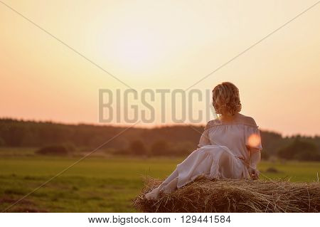 Young beautiful girl lies on a haystack