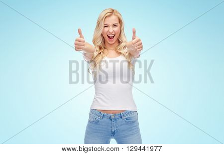 emotions, expressions, advertisement and people concept - happy smiling young woman or teenage girl in white t-shirt showing thumbs up with both hands over blue background