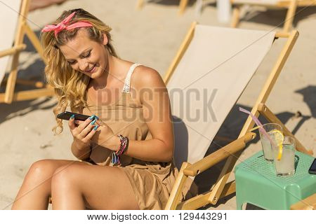 Pretty blond girl sitting on a sunbed on a beach holding a mobile phone texting and smiling