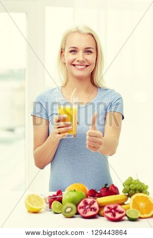 healthy eating, vegetarian food, dieting and people concept - smiling woman drinking fruit shake from glass at home showing thumbs up