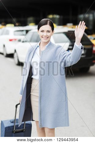 travel, business trip, people, gesture and tourism concept - smiling young woman with travel bag over taxi waving hand at airport terminal or railway station