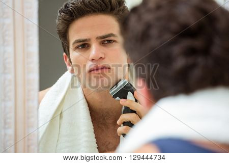 Reflection of smart young man in mirror shaving with trimmer