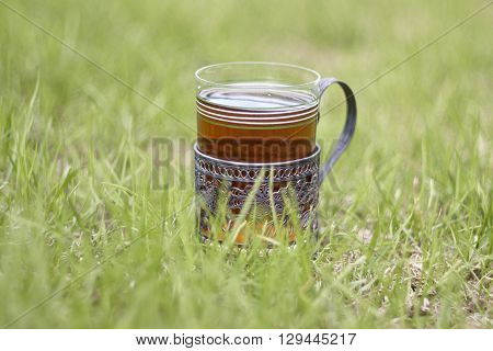 glass holder with glass of tea in lawn grass
