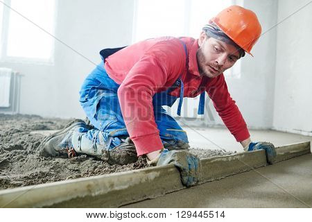 worker screeding indoor cement floor with screed