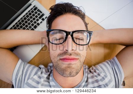 Close-up of man in spectacles sleeping on the floor with laptop