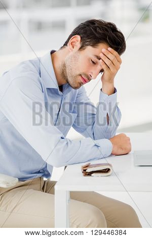 Tensed businessman sitting at table with hand on forehead in office