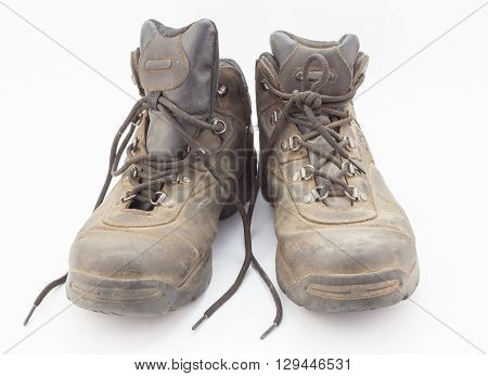 Dusty well used hiking boots isolated on white background