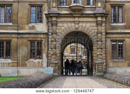 CAMBRIDGE, UK - DECEMBER 20 2015: Visitors walk through the main gate of Clare College, Cambridge, England.
