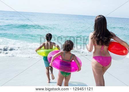 Mother with children holding swimming ring walking towards sea