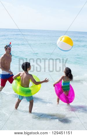 Father and children playing with beach ball on sea shore