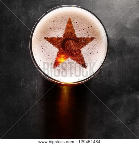 star symbol on foam in glass on black table, view from above