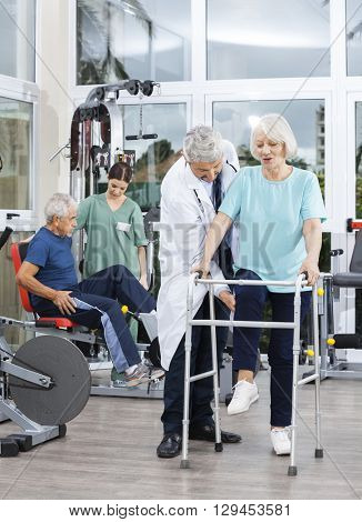 Physiotherapist Assisting Senior Woman With Walker In Fitness Ce