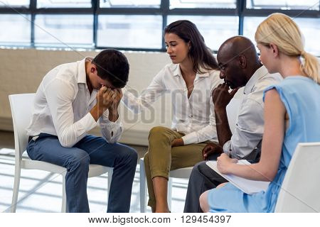 Colleagues comforting a unhappy man in office